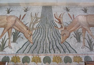 A mosaic picture of deer drinking at a stream flowing from the altar table.