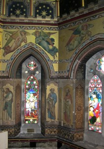 Detail of the painting in the chancel, showing figures of saints and the angels holding the 'Arms of Christ' above.
